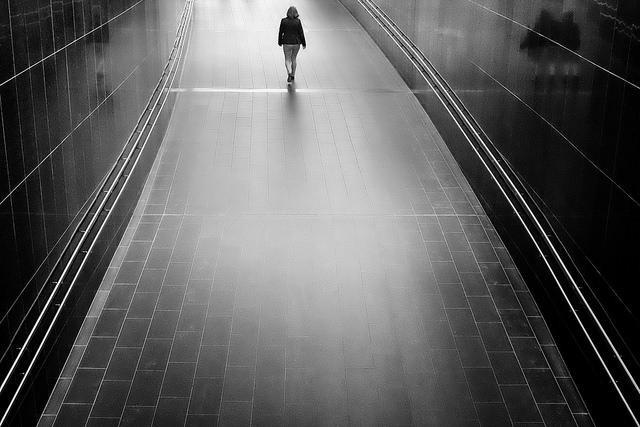 person walking alone in empty hallway.