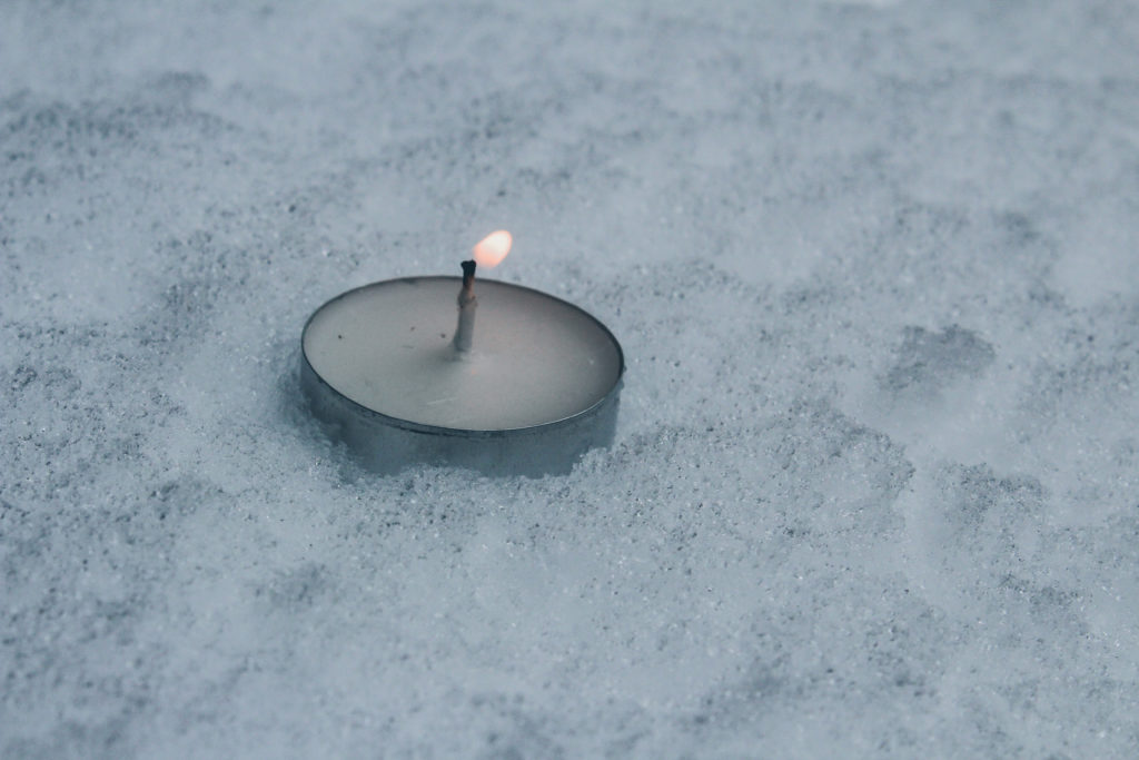 This is a photo of a small tea candle in the snow, with the wind blowing the flame and almost extinguishing it.